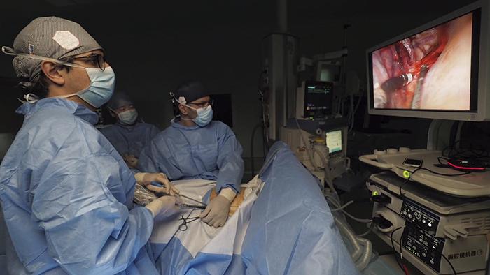 Skjerm er plassert ved pasientens hode, og operatør – assistent står på hver sin side av feltet.