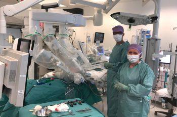 Figur 1. Assistent og operasjonssykepleier ved pasienten etter docking av robot. Hodeenden til pasienten til høyre på bildet.