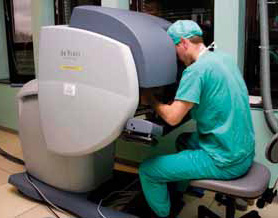 Bilde 1: Kirurgen sitter ved konsollen og opererer med spaker og pedaler.